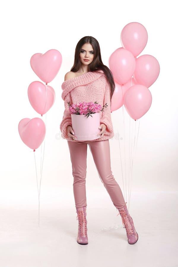 Jovem mulher bonita em flores cor-de-rosa da terra arrendada cor-de-rosa na caixa do chapéu sobre imagens de stock