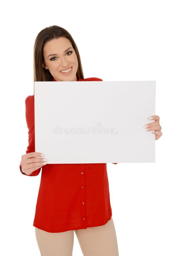 Jovem mulher bonita em pedaços de papel vazios da terra arrendada vermelha fotografia de stock royalty free