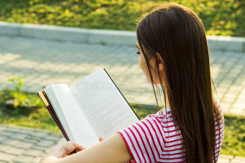 Jovem mulher bonita em t-shirt listrado que lê um livro no banco no parque Vista traseira imagem de stock