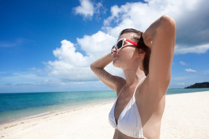 A jovem mulher bonita em um biquini branco relaxa na costa de foto de stock