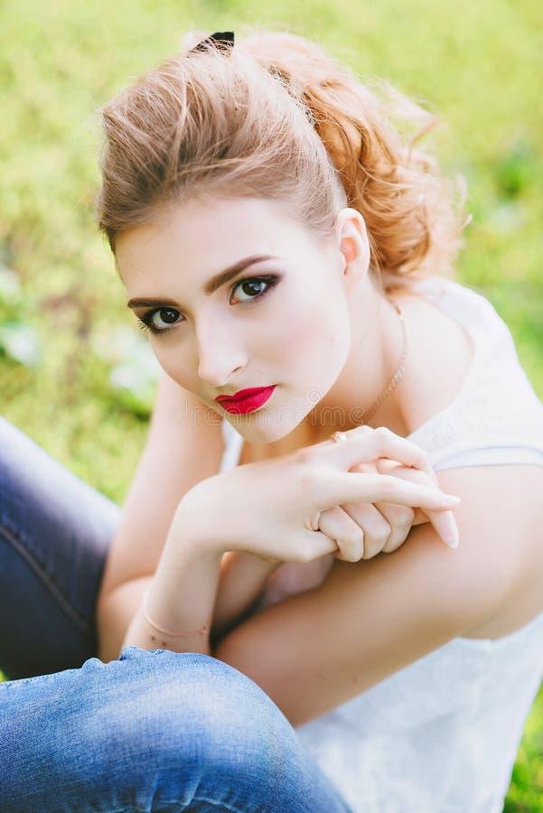 Jovem mulher bonita em um campo de futebol verde Retrato do close up de Bordos vermelhos imagem de stock