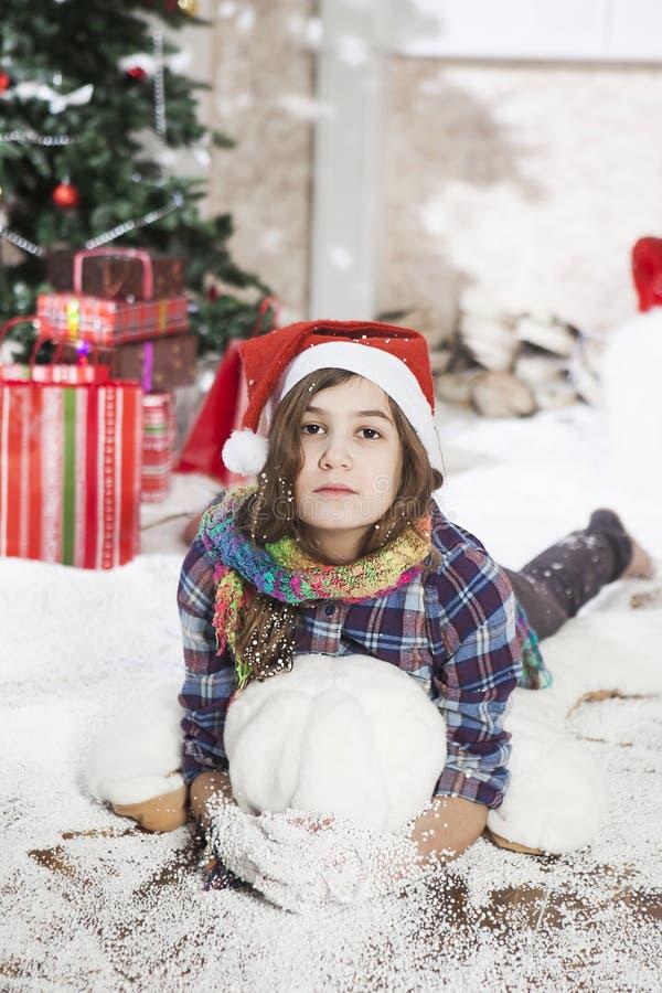 Jovem mulher bonita em um chapéu de Santa que encontra-se no assoalho próximo imagens de stock
