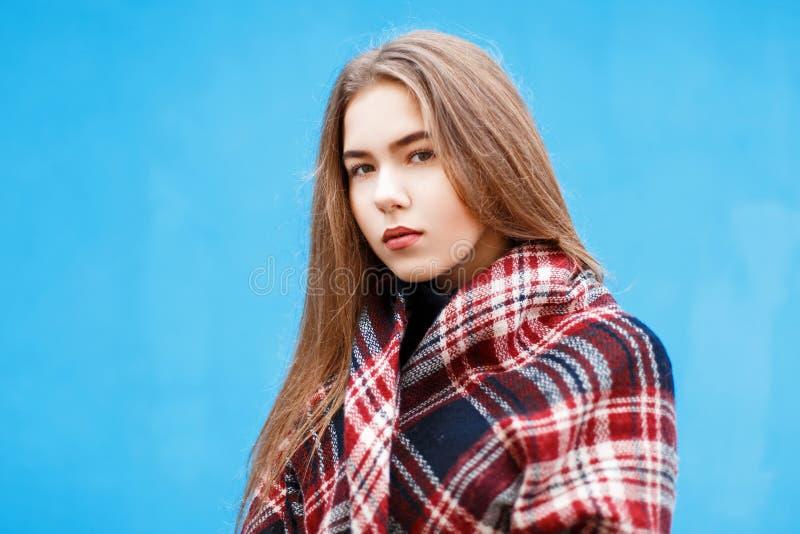 Jovem mulher bonita em um lenço morno perto de uma parede azul fotos de stock royalty free