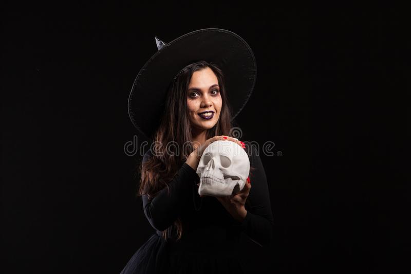 Jovem mulher bonita em um traje da bruxa para o partido do Dia das Bruxas que faz a feitiçaria má imagem de stock royalty free