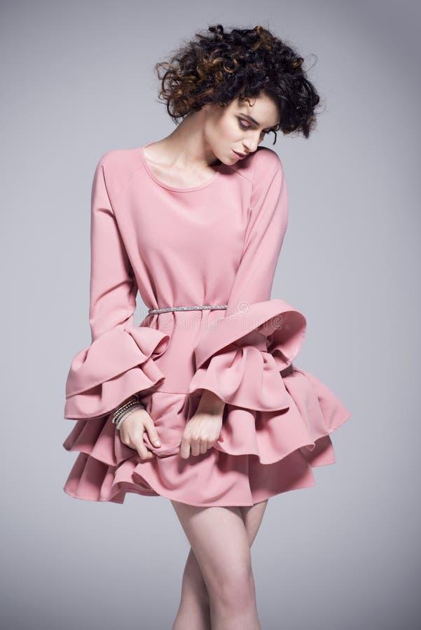 Jovem mulher bonita em um vestido cor-de-rosa com folhos fotos de stock