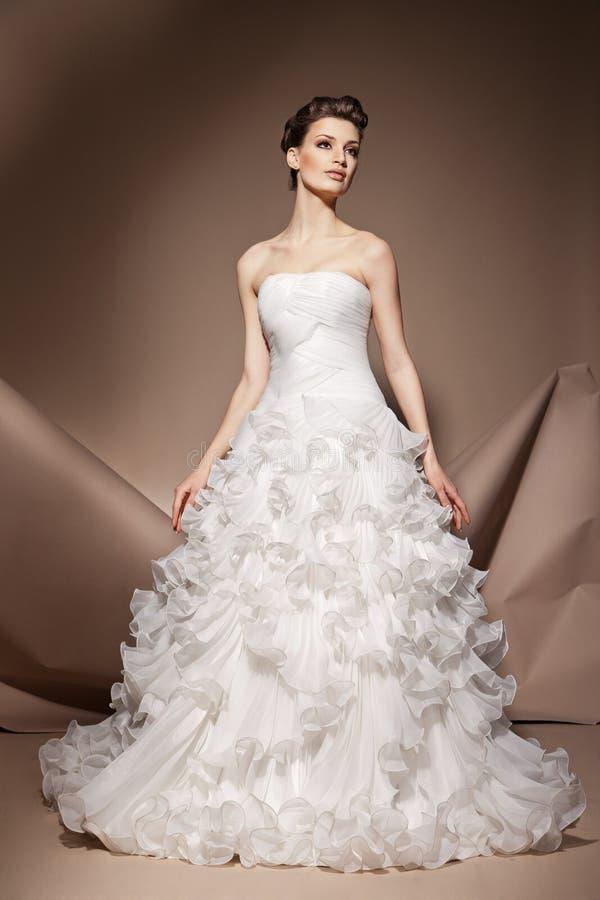 A jovem mulher bonita em um vestido de casamento fotografia de stock