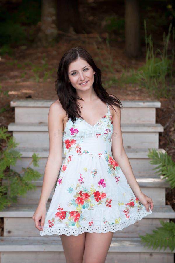 Jovem mulher bonita em um vestido do verão na frente das etapas de madeira imagens de stock royalty free