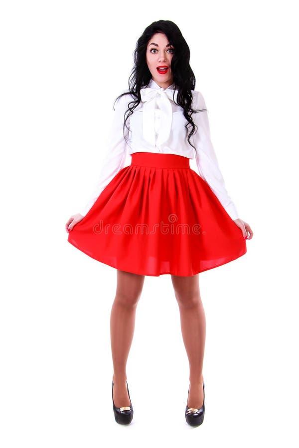 Jovem mulher bonita em uma blusa branca e em uma saia vermelha fotos de stock royalty free