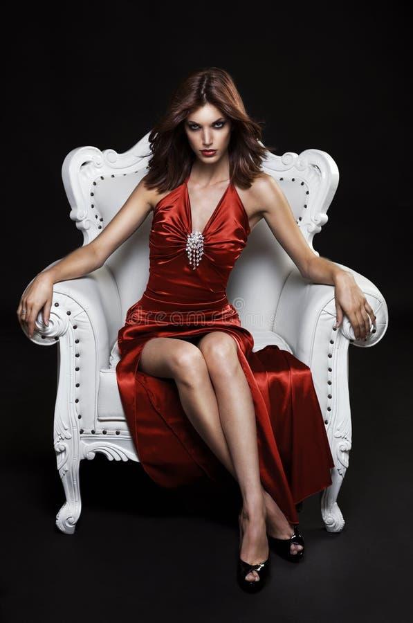 Jovem mulher bonita em uma cadeira foto de stock