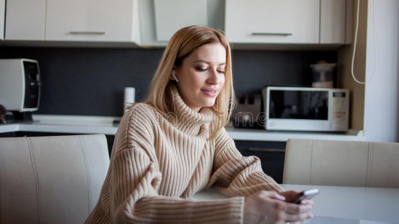 A jovem mulher bonita em uma camiseta acolhedor senta-se na cozinha e usa-se fones de ouvido sem fio para o smartphone foto de stock