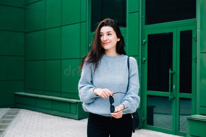 Jovem mulher bonita em uma camiseta azul de lãs que levanta na rua da cidade no fundo urbano da construção verde Senhora segura d fotos de stock royalty free