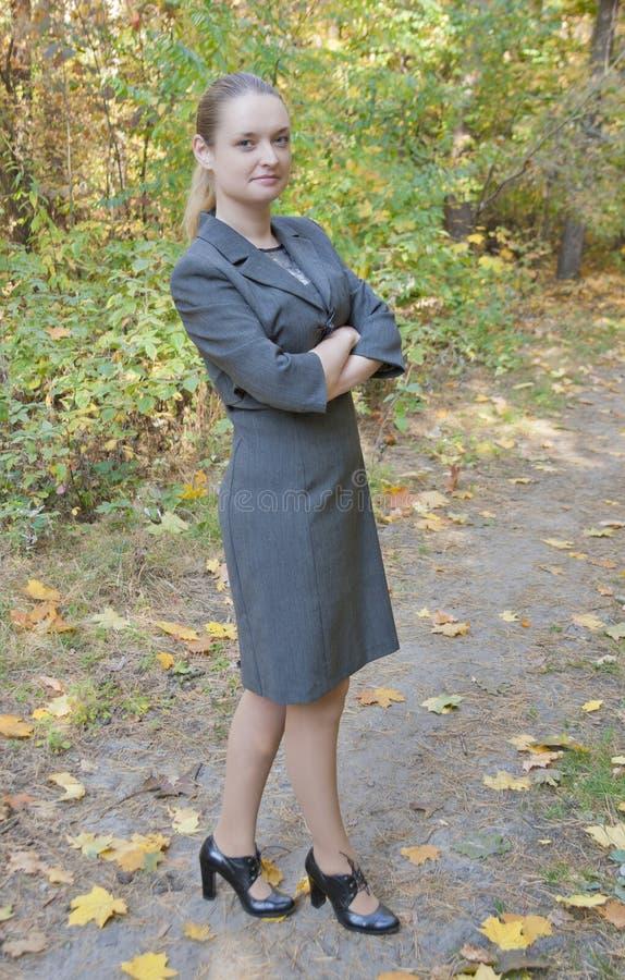 Jovem mulher bonita em uma posição cinzenta do vestido do negócio imagem de stock royalty free