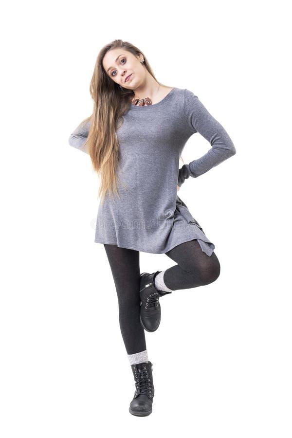 Jovem mulher bonita encantador bonito na túnica cinzenta que levanta em um pé fotografia de stock royalty free