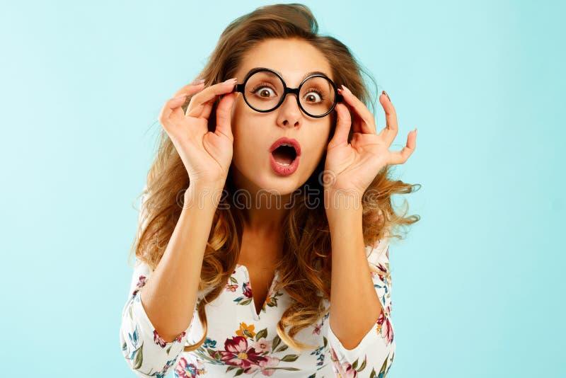 Jovem mulher bonita engraçada que guarda em volta dos vidros sobre o backgro azul fotos de stock royalty free