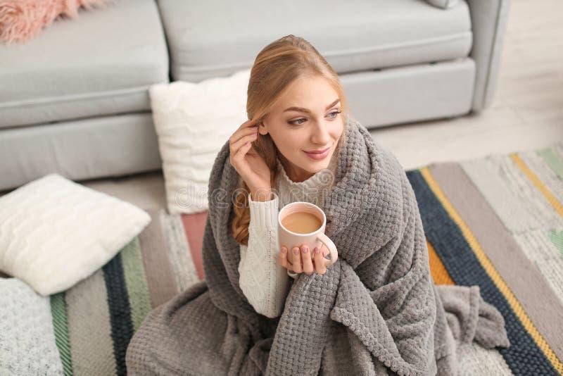 Jovem mulher bonita envolvida na manta que senta-se com a xícara de café no assoalho em casa imagem de stock royalty free