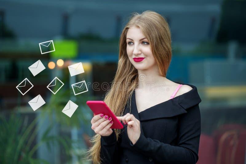 A jovem mulher bonita escreve mensagens em linha O conceito do Internet, tecnologia, redes sociais, uma comunicação e imagem de stock