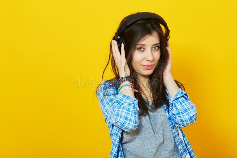 A jovem mulher bonita escuta e aprecia a música fotos de stock royalty free