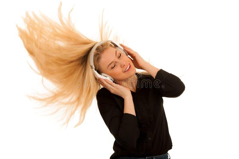 A jovem mulher bonita escuta a música em fones de ouvido e em dan fotografia de stock