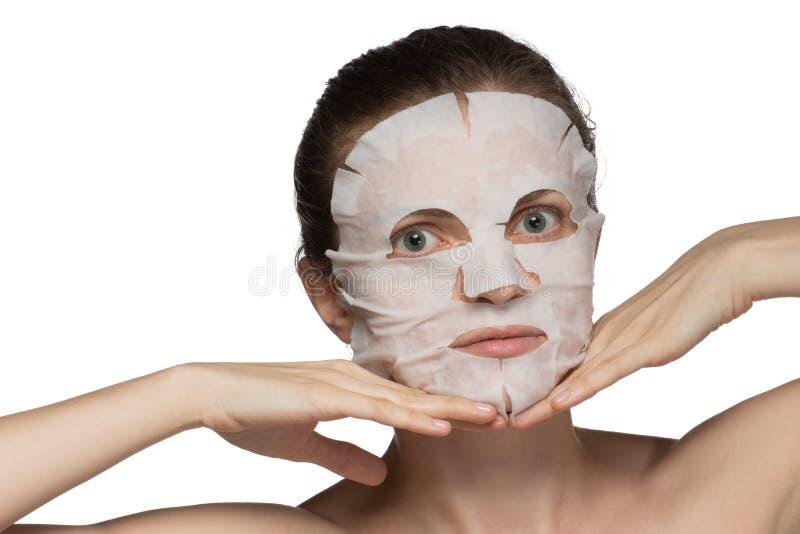 A jovem mulher bonita está aplicando uma máscara cosmética em uma cara na fotografia de stock royalty free