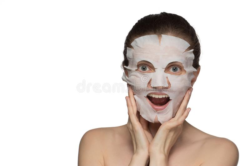 A jovem mulher bonita está aplicando uma máscara cosmética em uma cara na foto de stock royalty free