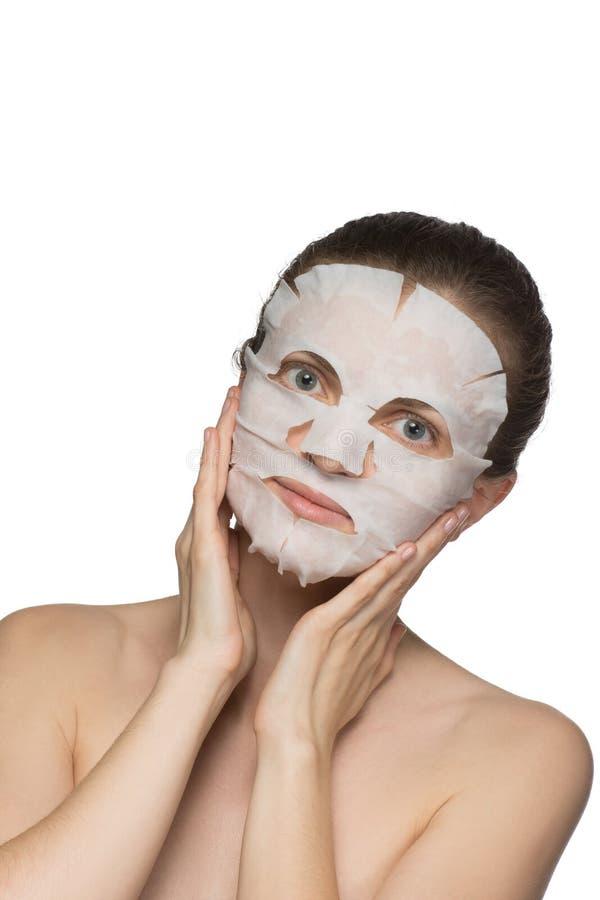 A jovem mulher bonita está aplicando uma máscara cosmética em uma cara na foto de stock