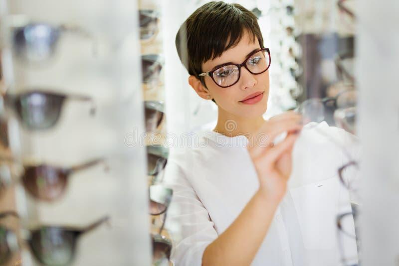A jovem mulher bonita está escolhendo vidros novos na loja do sistema ótico fotografia de stock royalty free