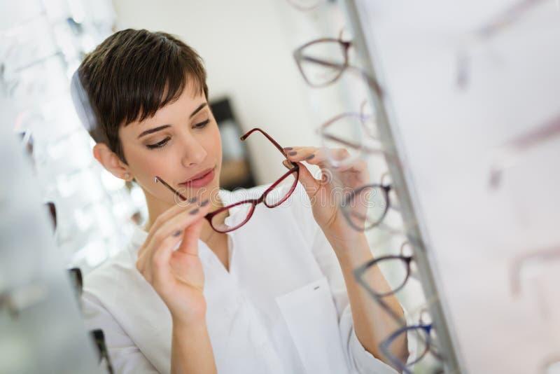 A jovem mulher bonita está escolhendo vidros novos na loja do sistema ótico imagens de stock royalty free