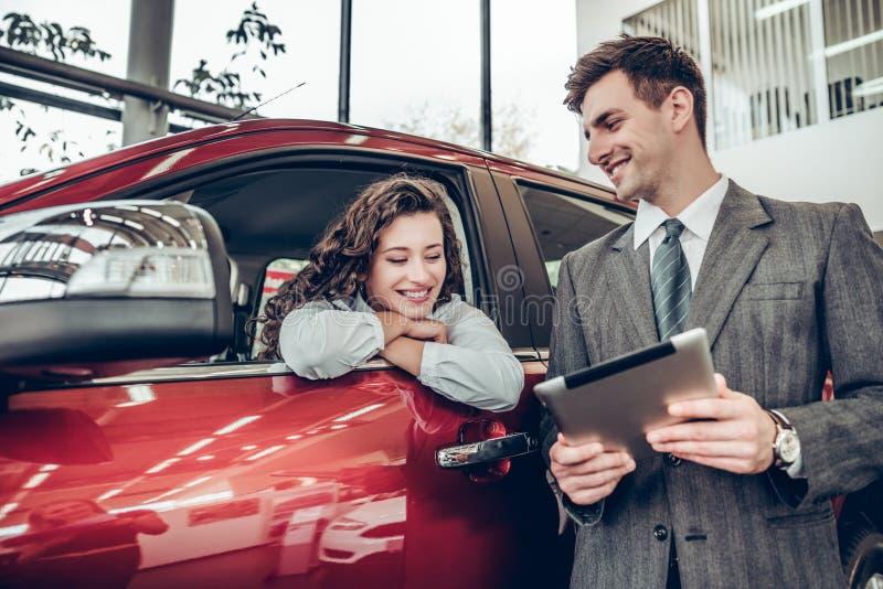 A jovem mulher bonita está falando ao gerente de vendas considerável ao escolher um carro no negócio fotografia de stock royalty free