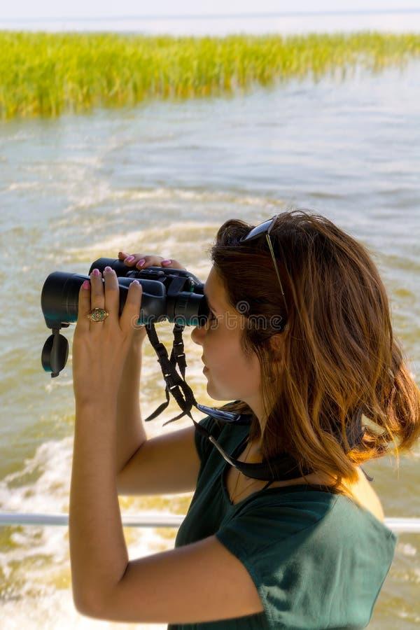 A jovem mulher bonita está olhando através dos binóculos da plataforma do barco fotos de stock