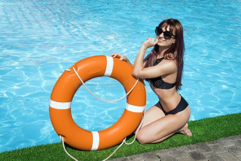 A jovem mulher bonita está sentada na beira da piscina com uma linha de vida sob a luz do sol sobre o fundo da água azul imagem de stock