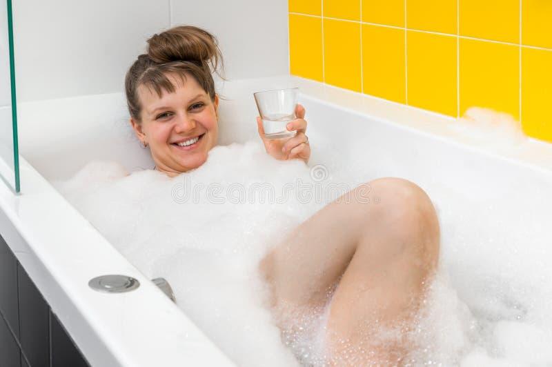 A jovem mulher bonita está tomando o banho de relaxamento com espuma fotos de stock