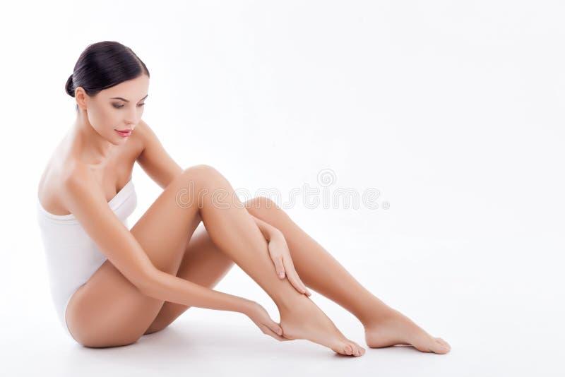 A jovem mulher bonita está tratando seus pés foto de stock