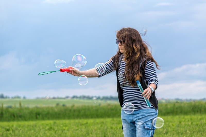 A jovem mulher bonita faz bolhas de sopro fotos de stock