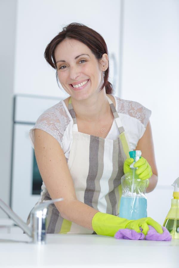 A jovem mulher bonita faz a casa da limpeza fotos de stock royalty free