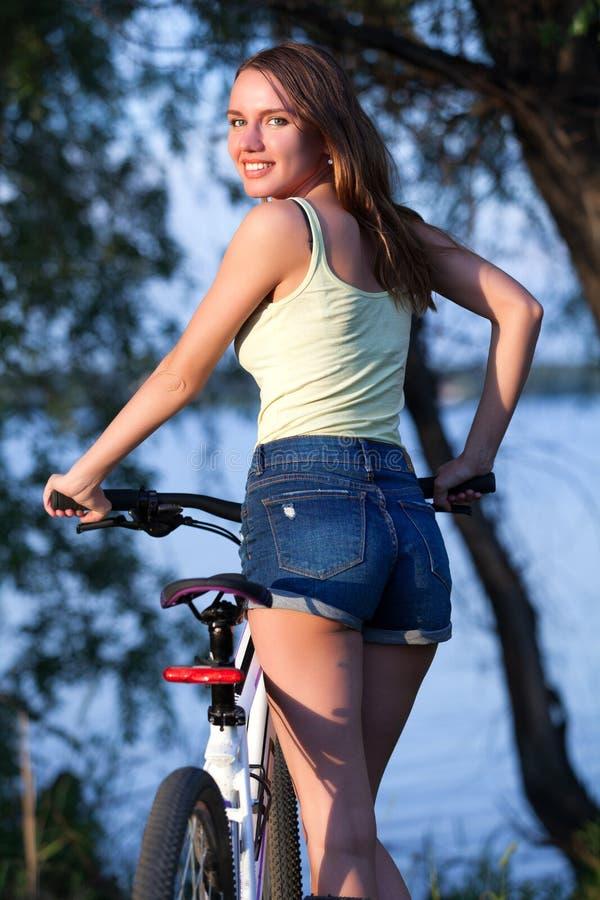 Jovem mulher bonita feliz com bicicleta imagens de stock