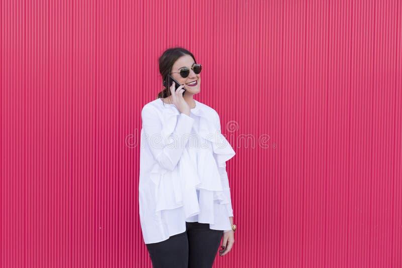 Jovem mulher bonita feliz da forma que tem uma utilização da conversação fotos de stock