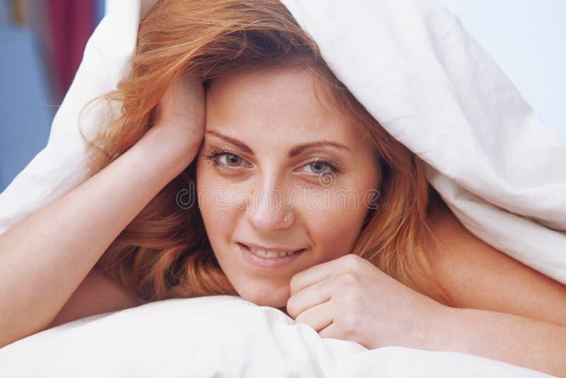A jovem mulher bonita feliz que acorda e descansada inteiramente nela seja fotografia de stock