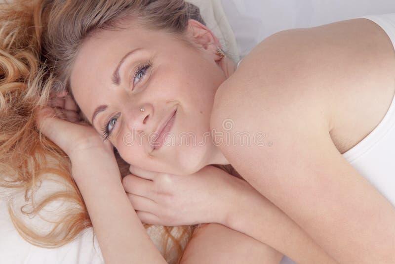 A jovem mulher bonita feliz que acorda e descansada inteiramente nela seja imagens de stock royalty free