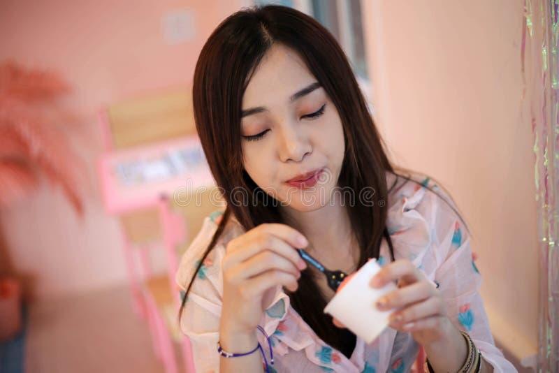Jovem mulher bonita feliz que come o gelado, delicioso, apreciando, felicidade, conceito de sorriso imagem de stock