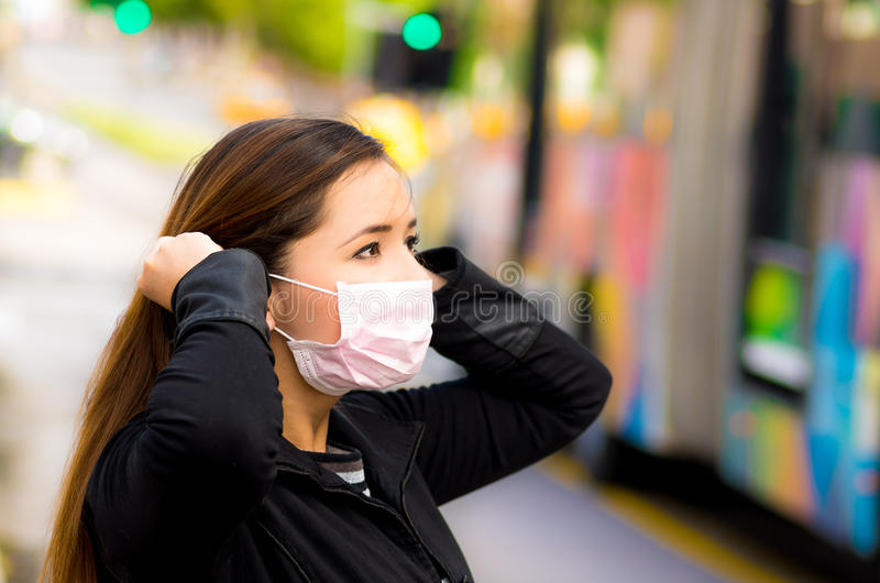 Jovem mulher bonita feliz que fixa sua máscara protetora na rua na cidade com poluição do ar com um ônibus borrado imagens de stock