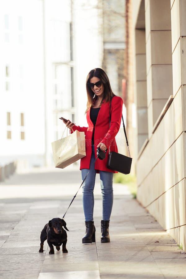 Jovem mulher bonita fresca que anda ao comprar a cidade com seu cão pequeno foto de stock royalty free