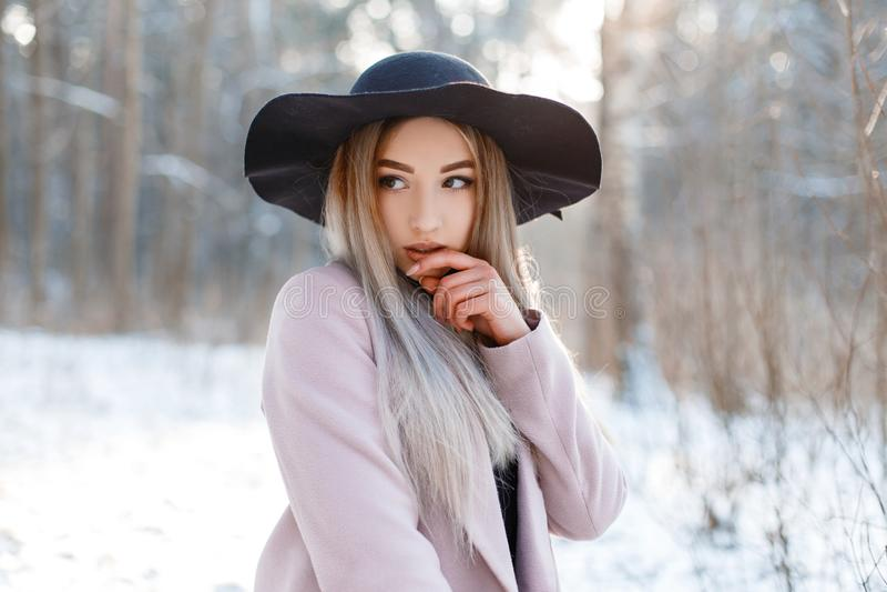 Jovem mulher bonita bonita glamoroso de surpresa em um chapéu negro luxuoso em um revestimento morno cor-de-rosa à moda que levan fotos de stock