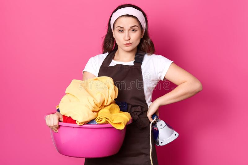 A jovem mulher bonita guarda a bacia cor-de-rosa com a lavanderia e o ferro, olhando a câmera ao estar isolada sobre o fundo cor- fotos de stock