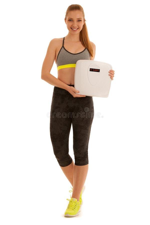 A jovem mulher bonita guarda uma escala como perdeu o peso isolado fotos de stock royalty free
