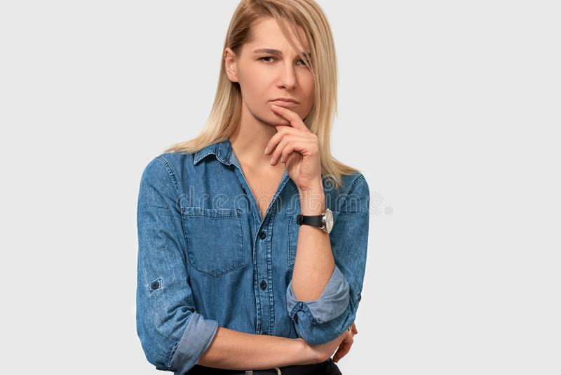A jovem mulher bonita infeliz do cabelo louro na camisa azul da sarja de Nimes com dedo dobrou olhar de sobrancelhas franzidas su fotos de stock