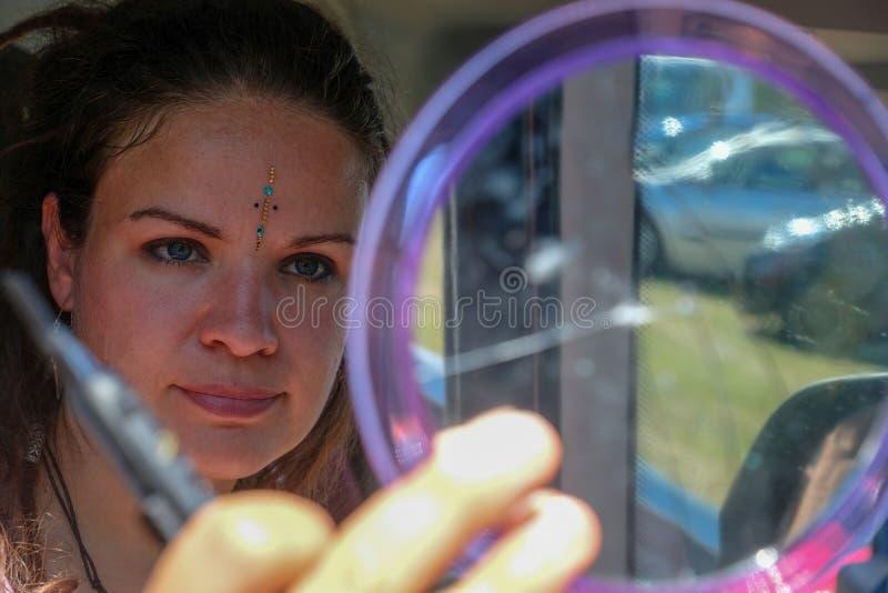 A jovem mulher bonita interessante olha si mesma no espelho e nas varas com as pedras de brilho da faca do cortador na cara fotografia de stock royalty free