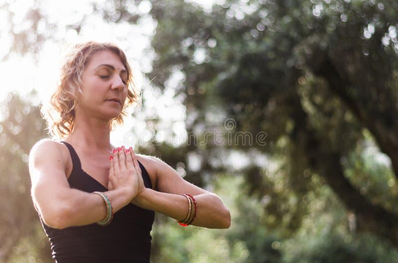 A jovem mulher bonita medita no asana Padmasana da ioga - a pose de Lotus na plataforma de madeira no parque do outono imagens de stock royalty free