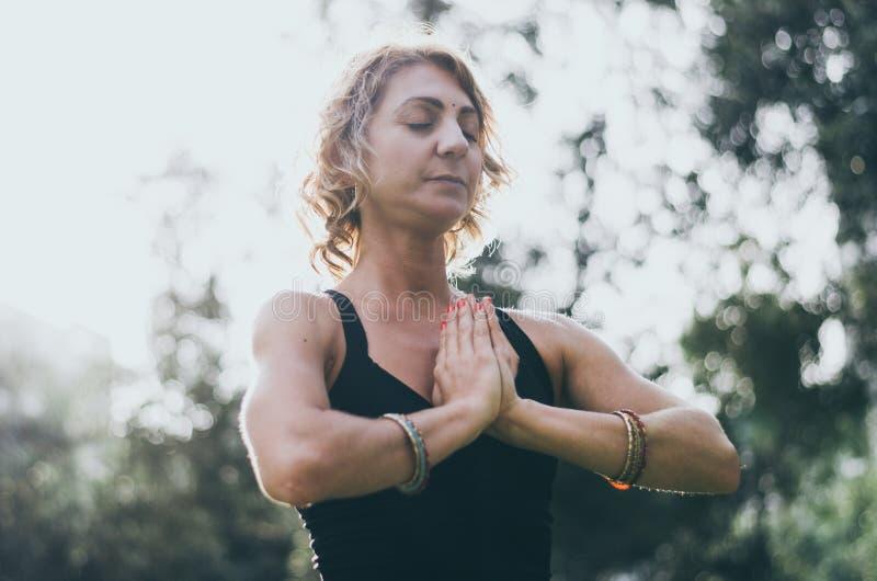 A jovem mulher bonita medita no asana Padmasana da ioga - a pose de Lotus na plataforma de madeira no parque do outono fotos de stock
