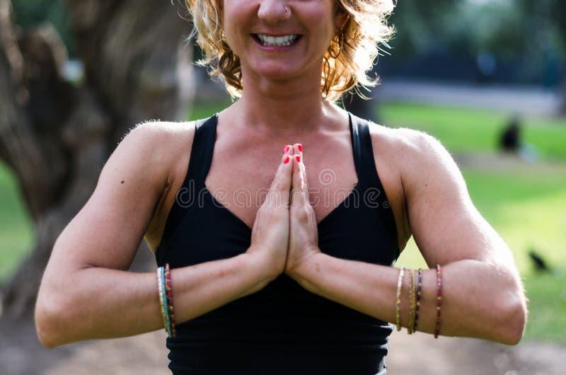 A jovem mulher bonita medita no asana Padmasana da ioga - a pose de Lotus na plataforma de madeira no parque do outono foto de stock