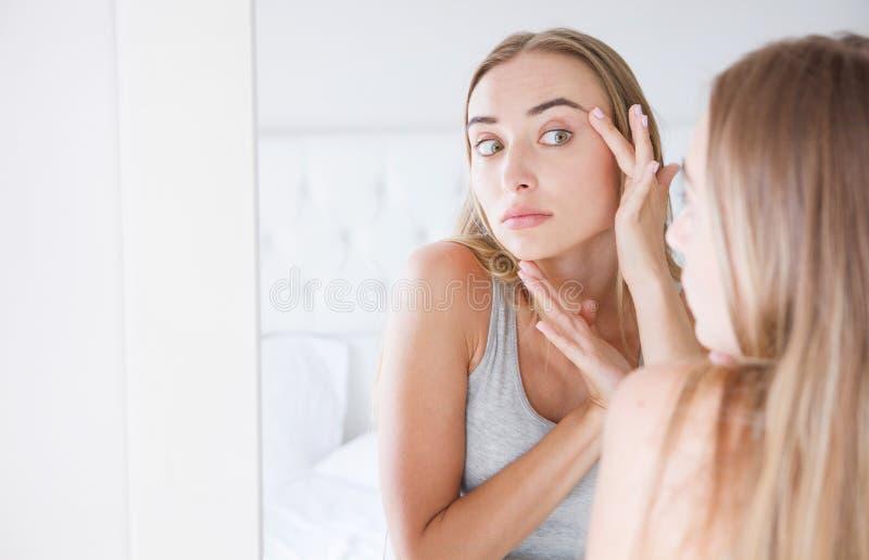 A jovem mulher bonita, menina está tocando em sua cara ao olhar o espelho Problema em sua pele fotografia de stock royalty free